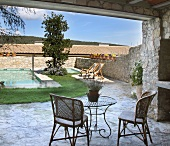 Basketwork chairs and metal bistro table on enclosed stone terrace with loungers and pool in background