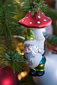 Bauble with dwarf motif hanging from fir branch