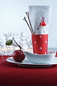 Red and white napkin in red beaker with white polka dots in white bowl on red felt cloth