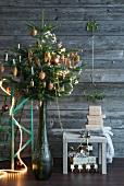 Geschmückter Weihnachtsbaum in Vase neben Hocker mit Geschenken vor schlichter Holzwand