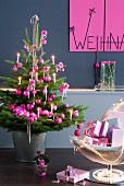 Geschmückter Weihnachtsbaum mit pinkfarbenen Kugeln neben Sessel mit Geschenken vor grauer Wand und Weihnachtsgruss an pinkfabener Tafel