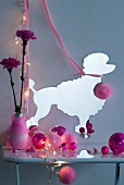 Various pink Christmas baubles on console table in front of paper silhouette of poodle on grey wall