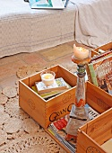Lit candle on candlestick amongst crates of books on floor