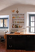 Kitchen counter with black cupboard doors below rustic shelves flanked by windows