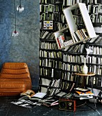 Photographic wallpaper with bookcase motif; slanted shelves mounted on wall & vintage leather chair