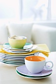 Teacups and stacked plates on table