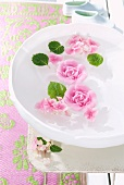 Rose-shaped, scented floating candles in bowl of water