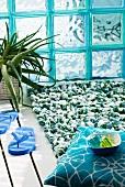 Grün-weisse Badematte mit Schlaufen vor türkisfarbenen Glasbausteinen