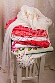Stack of clothes, scarf and fabric heart on wooden stool