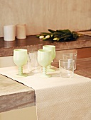 Painted wine glasses and water glasses on runner on concrete slab