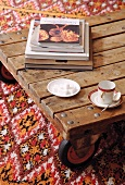 Mocha cup and saucer and sugar cubes on low wooden table with castors on patterned rug
