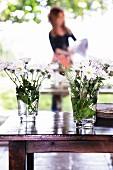 weiße Blumensträußchen in Trinkgläsern auf glänzendem Holztisch auf der Terrasse