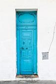 weiße Fassade mit strahlend blauer Eingangstür