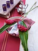 Gedeck mit tropischen Blüten auf gemusterter Stoffserviette; marokkanische Silberkanne und Teegläser im Hintergrund