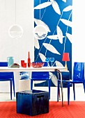 Dining table, stool, plastic chairs & photographic wallpaper in interior in shades of blue & red