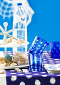 Table with blue tablecloth, blue glasses & seashells on cake stand