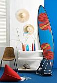 Strohhüte an Wand hängend & Surfboard neben Ablagetischchen mit Glasvasen