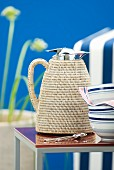 Thermos jug with raffia cover on side table