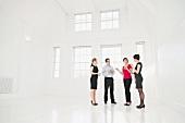Junge Leute in Business-Kleidung stehen in einem weissen Raum