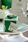 Gift box with ribbon and name tag on place setting with wine glass