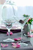50s-style cocktail glasses and petals on grey table runner