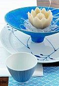 Candle shaped like lotus flower in blue dish and china with white and blue painted detail