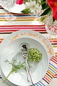 Dessert cutlery and flower in dish on multicoloured striped tablecloth