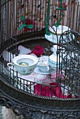 Tealight holders made from old teacups in birdcage