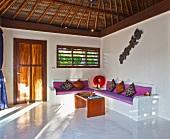 Sitzbänke mit Polsterauflage und bunten Sitzkissen in einem minimalistisch eingerichteten Wohnzimmer