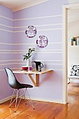 Black Bauhaus shell chair in front of console table in corner of room with lilac and white striped wall