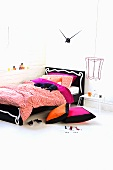 Modern bed with black and white frame and colourful cushions on floor in corner of white room