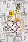 Wall-mounted drawer unit with butterfly motifs on front; wallpaper with pattern of picture frames
