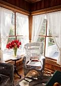 Weisser Korbstuhl am Fenster, Vase mit roten Blumen auf Beistelltisch