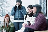 Junge Leute trinken warmen Tee vor einer Hütte