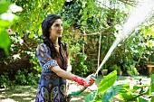 Woman watering plants in tropical garden
