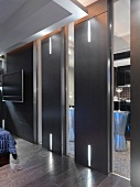 Designer bedroom with black sliding doors and integrated LED strip lighting in front of an en suite bathroom