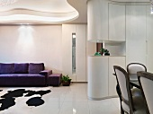 Open living room with futuristic ceiling design and dining area in front of a cupboard serving as a room divider
