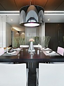 Designer hanging lamp with a black shade over a set dining table
