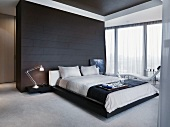 Breakfast tray on a double bed in front of a black tiled room partition in a minimalist bedroom