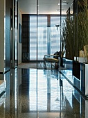 Lobby with a highly polished stone floor and view through a glass wall partition of armchairs