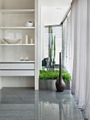 White bookshelves serving as a room partition next to floor vase and plant pot on a high gloss stone floor