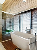 Free standing bathtub in front of a bank of windows with closed blinds in a modern bathroom with a wooden ceiling