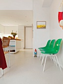 Green plastic shell chairs along a wall on a white floor in an open living room