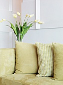 Pillows on an a couch upholstered in light-colored velvet