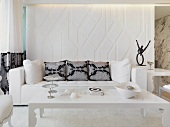 Post modern coffee table in front of a sofa with pillows by a white room divider with indirect lighting