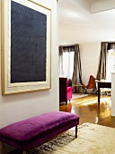 Blick in den offenen Wohnraum; davor eine gepolsterte Sitzbank mit violettem Samtbezug und mit darüberhängendem, modernen Wandbild