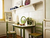 Simple kitchen table and green-painted chairs against tiled wall and below white shelf