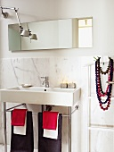 Modern washstand with towels hanging on metal base frame against marble wall panel