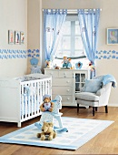 Play mat in front of white cot and armchair next to half-height chest of drawers below window in country-style nursery