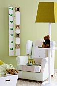 Child's bedroom - toys on standard lamp with shelf in front of armchair against green wall with height chart